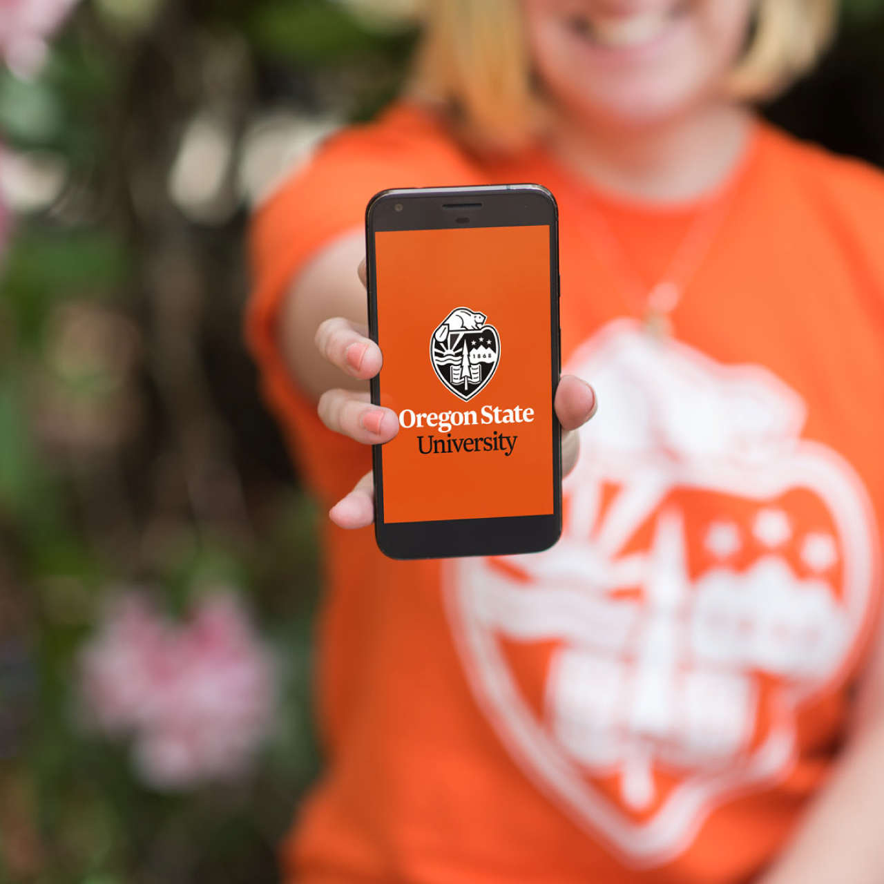 Woman holding phone displaying the OSU logo
