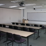 classroom with long tables and whiteboard